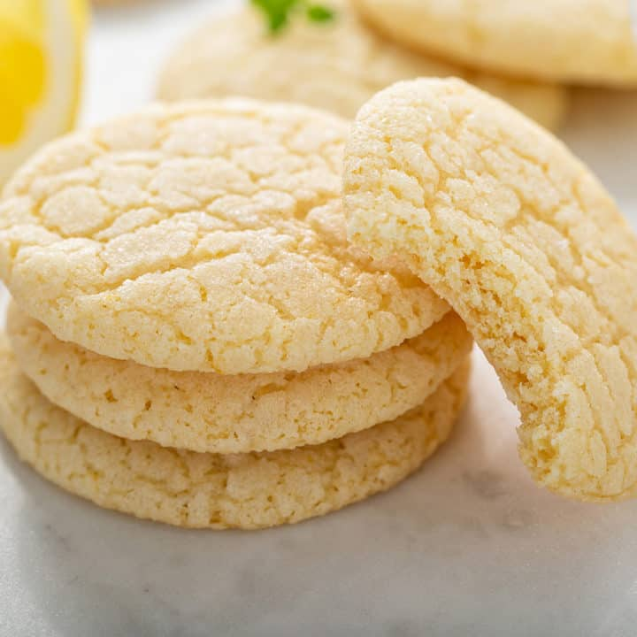 Chewy lemon sugar cookies in a stack. A cookie with a bite out of it is leaning against the stack.