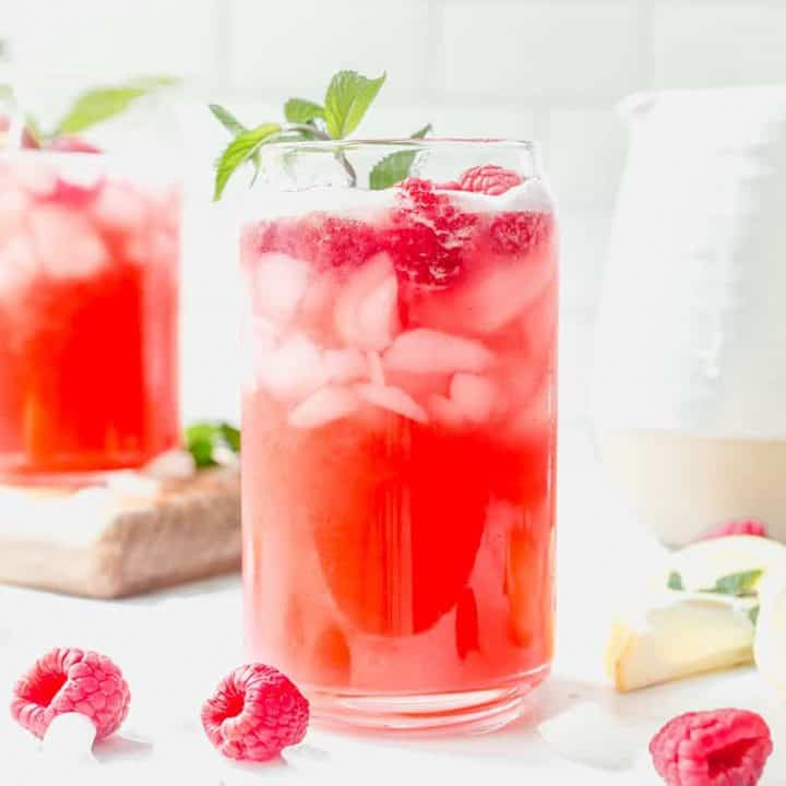 Glass of raspberry lemonade garnished with a sprig of mint on a white countertop, surrounded by fresh raspberries and another glass and pitcher of lemonade in the background