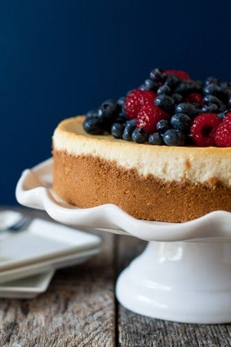 Lemon cheesecake topped with berries on a white cake stand