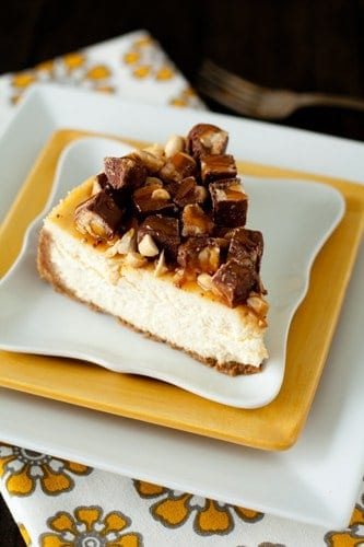 Slice of Snickers cheesecake on a stack of yellow and white plates