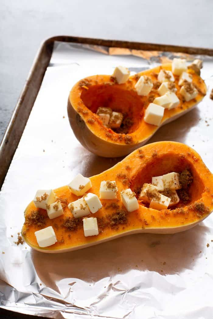 Halved butternut squash topped with butter cubes and brown sugar on a foil-lined baking sheet