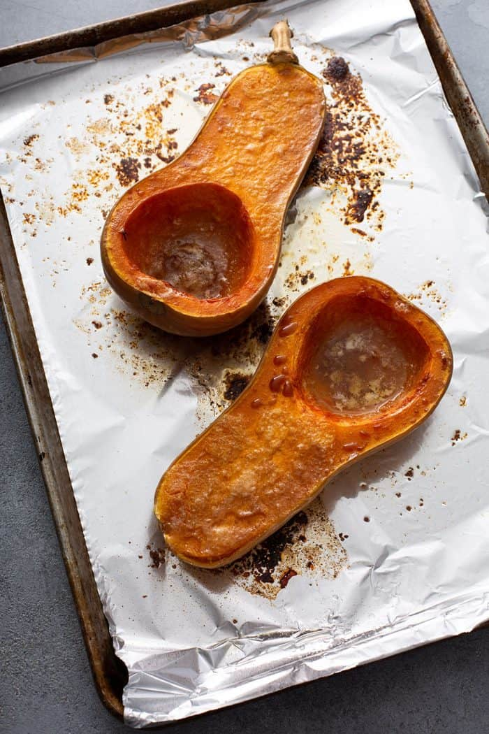 Roasted butternut squash halves on a foil-lined sheet tray