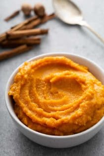 Butternut squash puree in a white bowl with whole spices and a spoon in the background