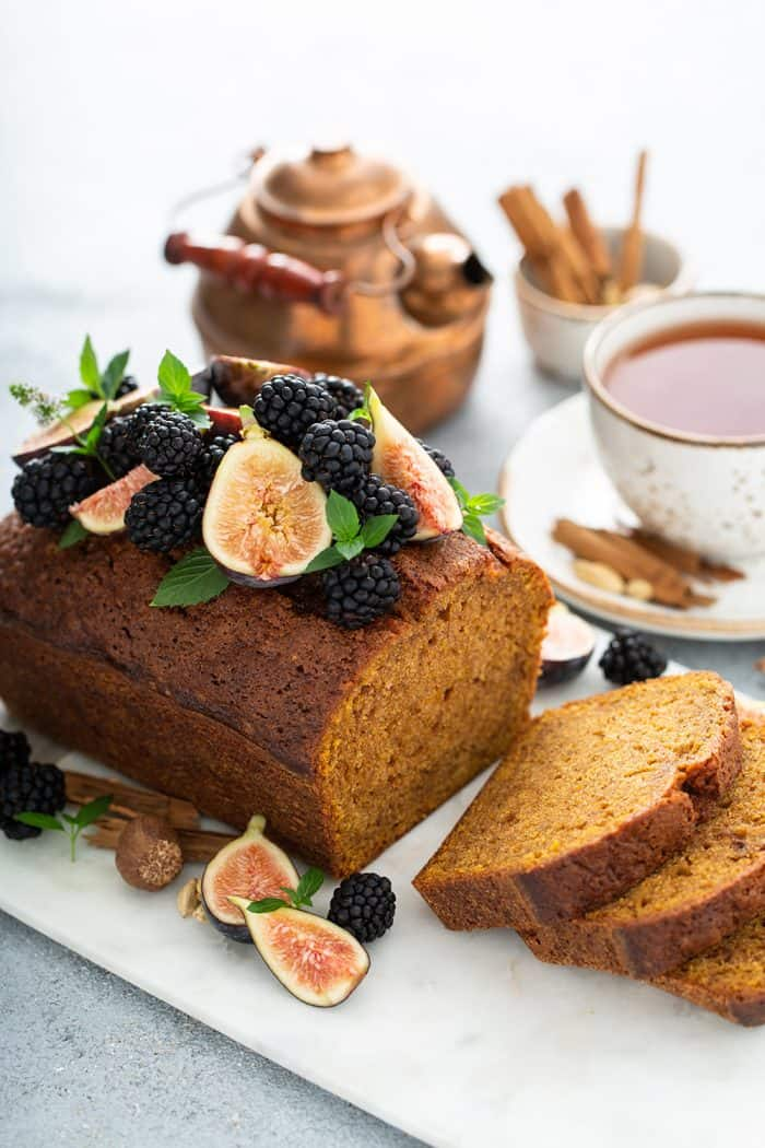 Sliced loaf of butternut squash bread topped with figs and berries on a cutting board with a teapot and cup of chai in the background