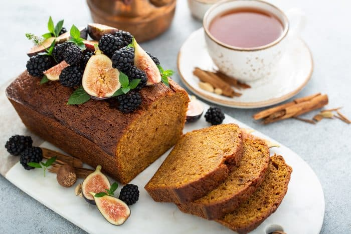 Loaf of butternut squash bread topped with figs and blackberries on a marble board with a cup of chai in the background
