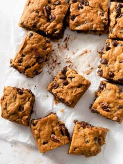 Sliced pumpkin blondies with chocolate chips on parchment paper