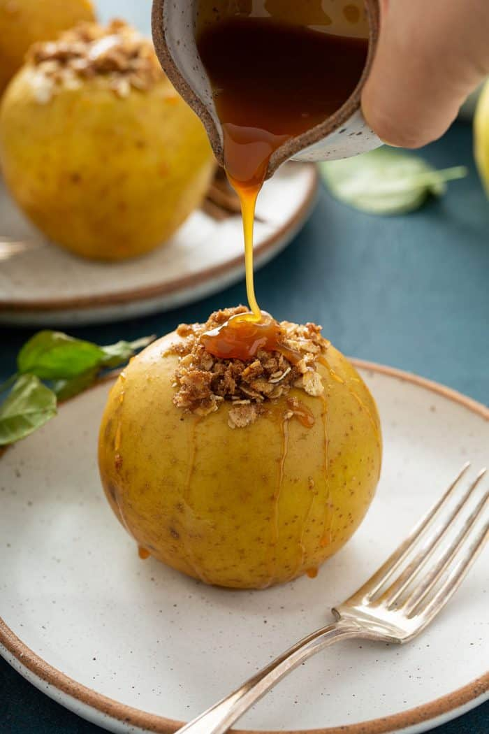Hand pouring caramel sauce onto a plated baked apple