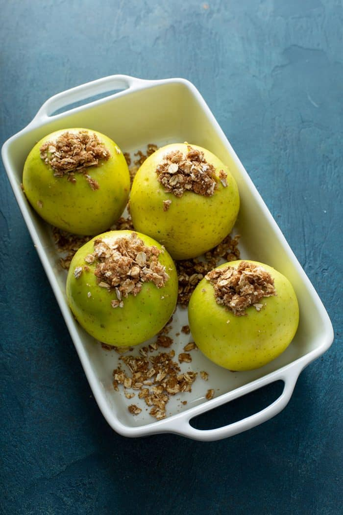 Crumble-stuffed apples in a white baking dish, ready to be baked