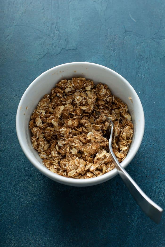 Oat crumble for baked apples in a white bowl