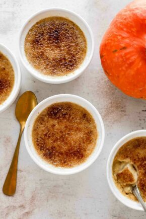 Pumpkin creme brulee in white ramekins, next to a spoon and a pumpkin