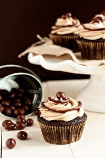 Cafe mocha cupcake in front of a spilled container of chocolate covered espresso beans and a cake stand full of cupcakes