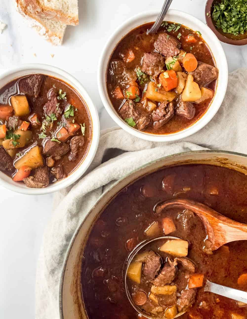 Pot of Guinness beef stew next to small bowls of stew