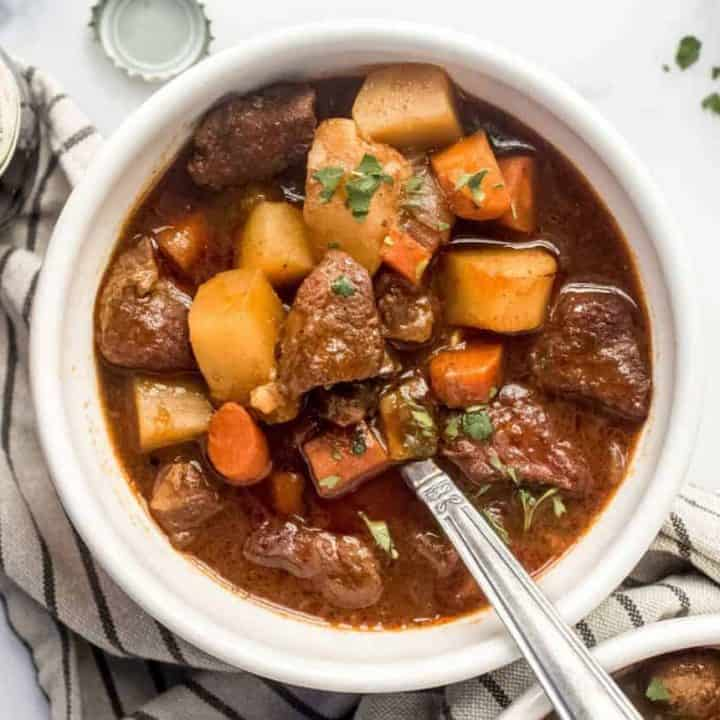 Guinness stew full of carrots and potatoes in a white bowl