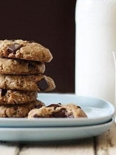 Stack of almond cookies on a plate next to a glass of milk