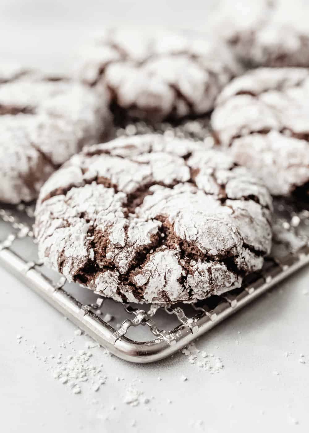 Close up view of a chocolate crinkle cookie on a cooling rack