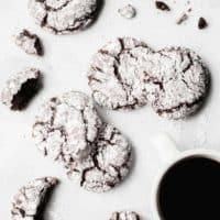 Chocolate crinkle cookies scattered on a white counter with a cup of coffee