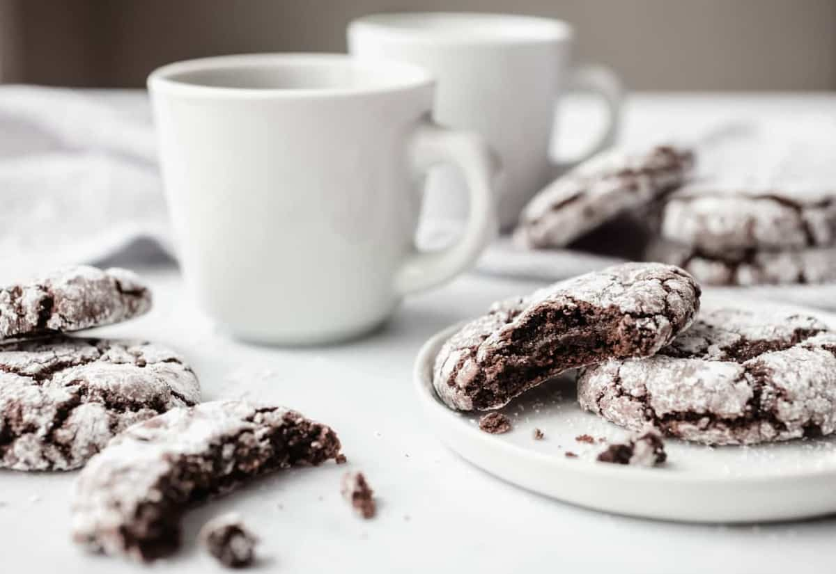 Chocolate crinkle cookies on white plates next to cups of coffee