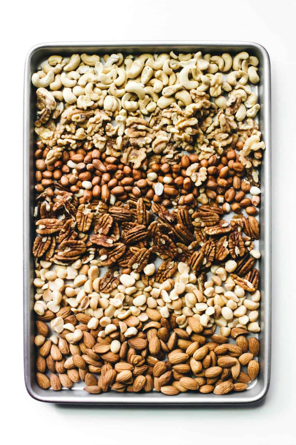 Assorted mixed, toasted nuts arranged on a sheet pan