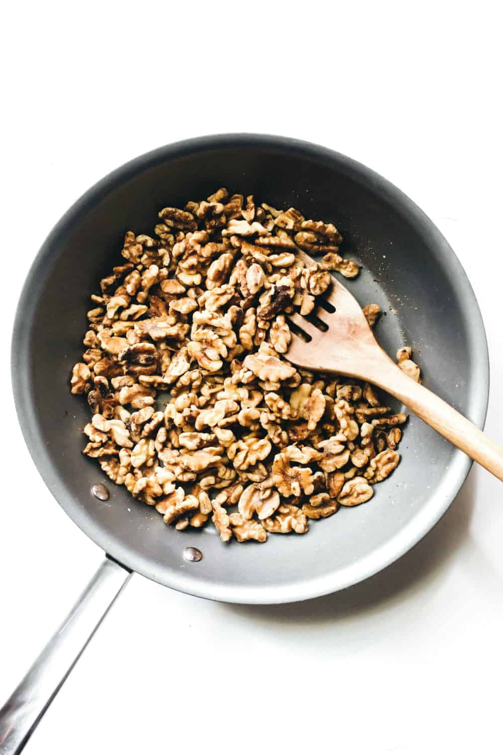 Walnuts in a skillet being stirred with a wooden spoon