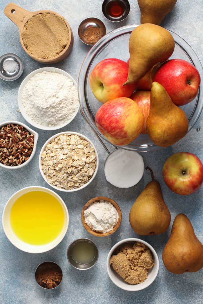 Ingredients for apple pear crisp on a blue countertop