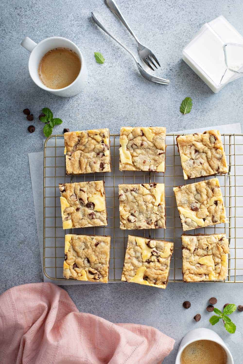 Overhead shot of sliced cookie dough cheesecake bars on a cooling rack