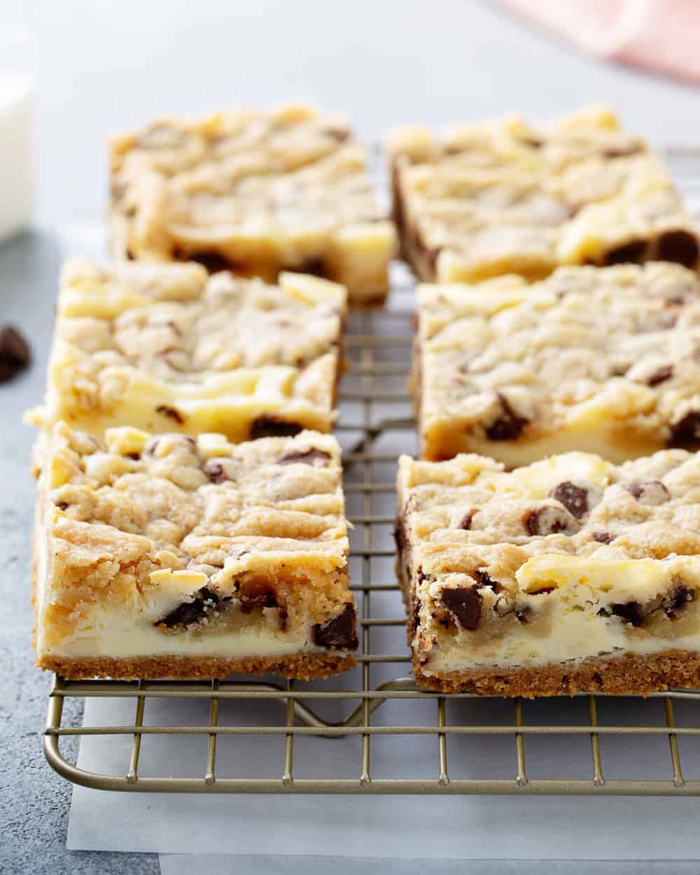 Close up of sliced cookie dough cheesecake bars on a cooling rack