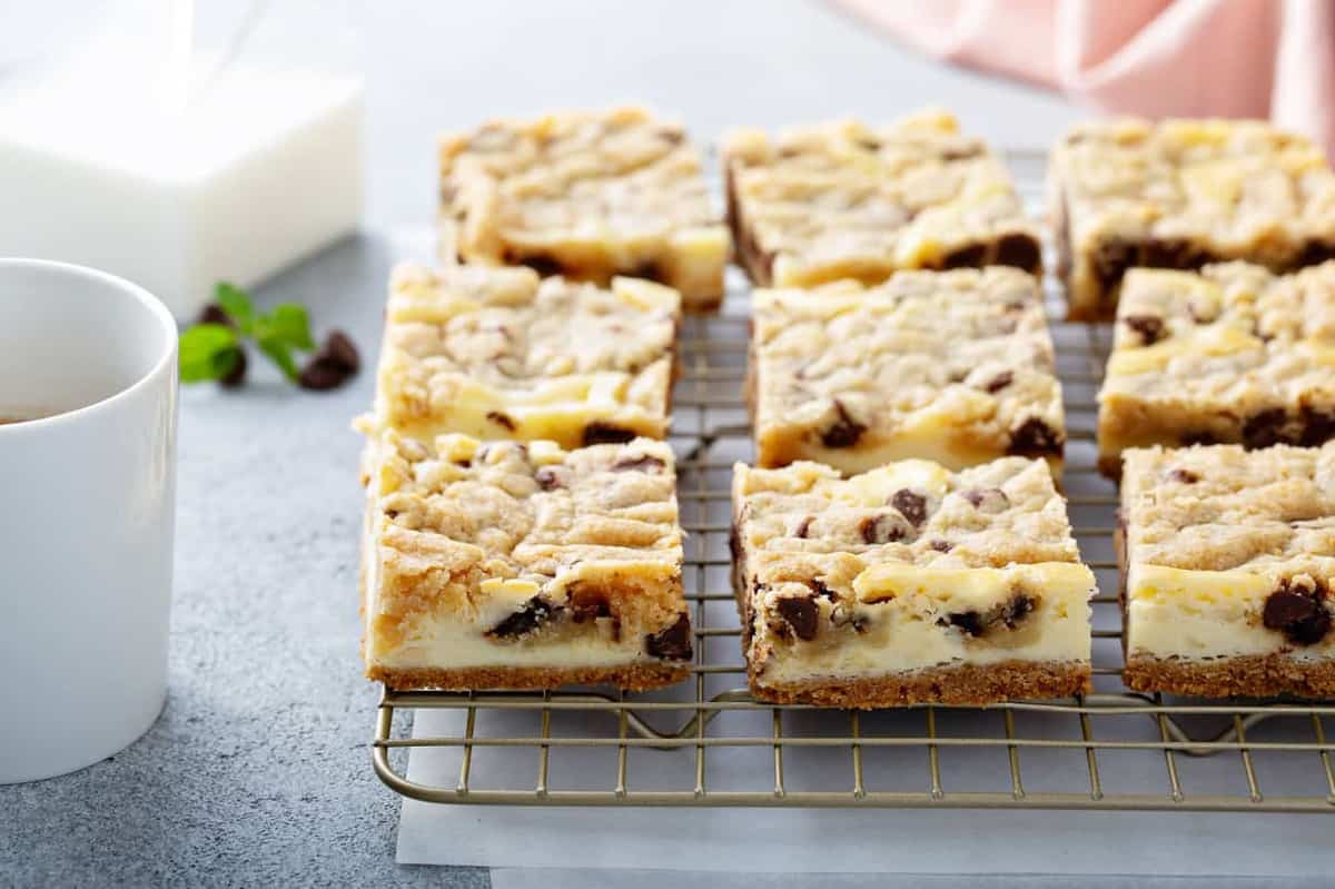 Sliced cookie dough cheesecake bars on a cooling rack over a piece of parchment paper