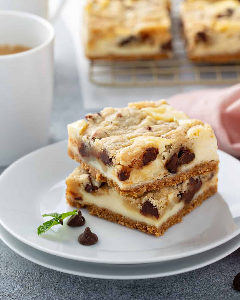 Two cookie dough cheesecake bars on a white plate