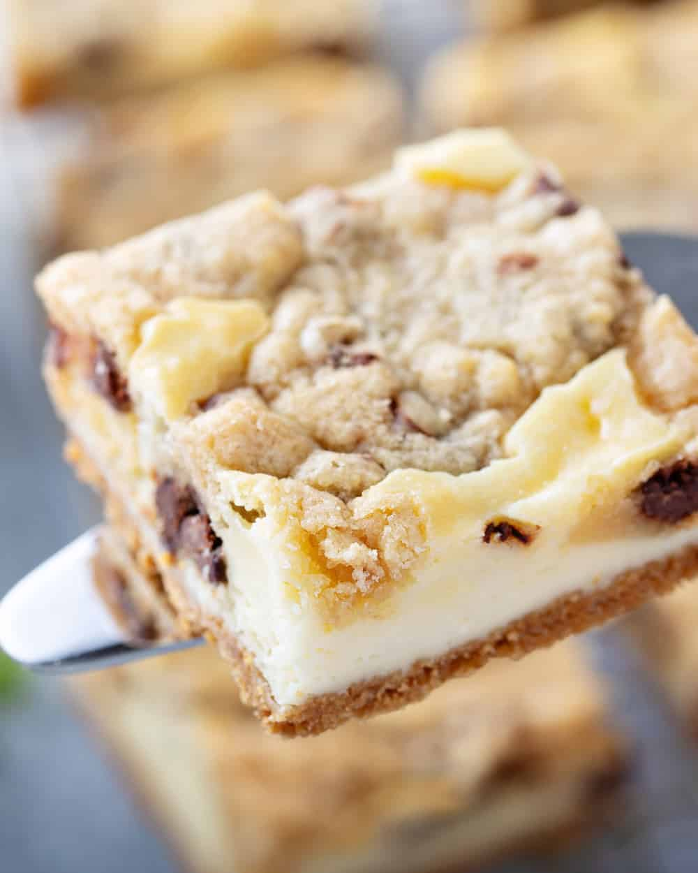 Knife lifting up a piece of cookie dough cheesecake bar