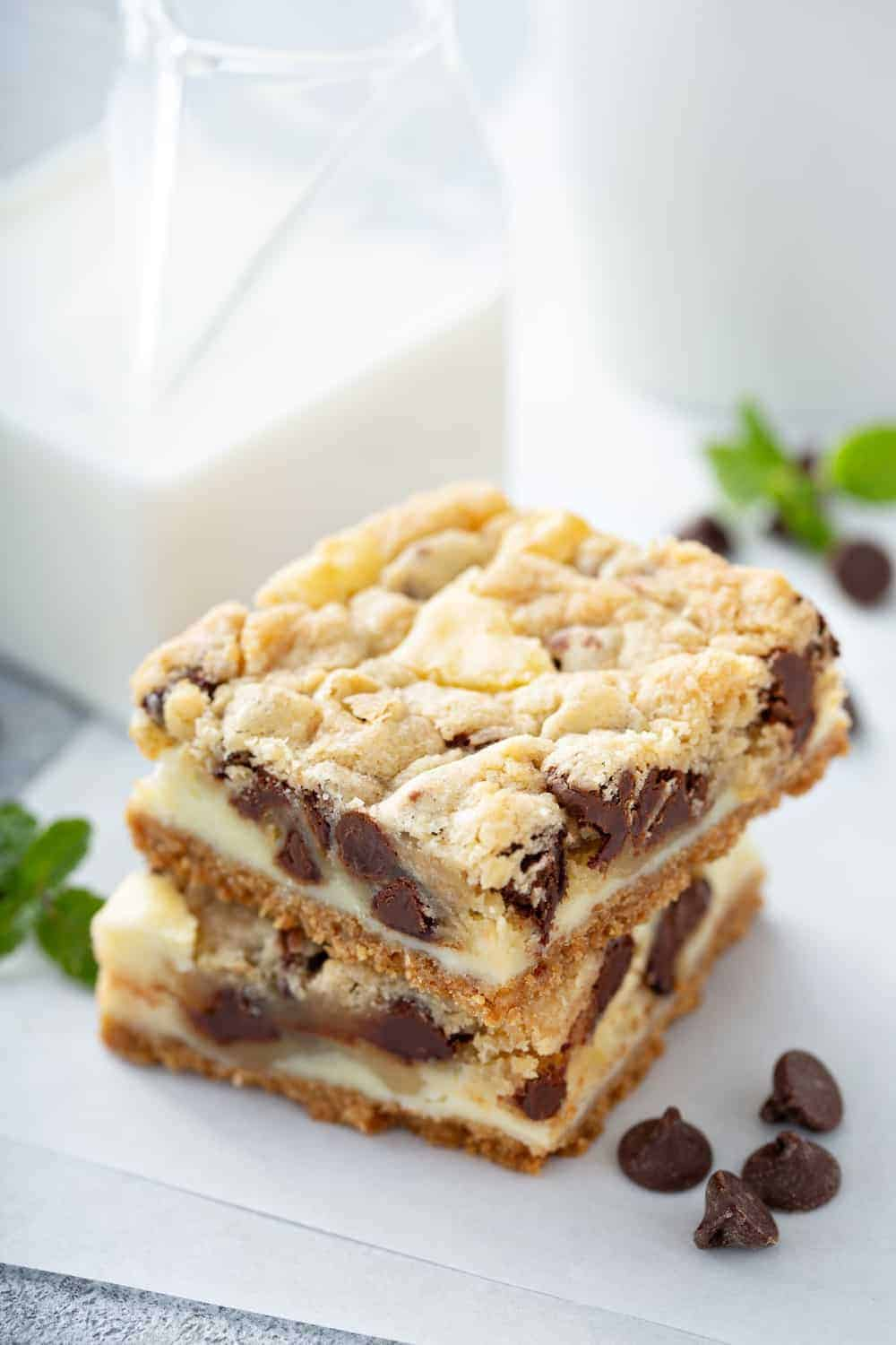 Close up of sliced cookie dough cheesecake bars on a piece of parchment paper