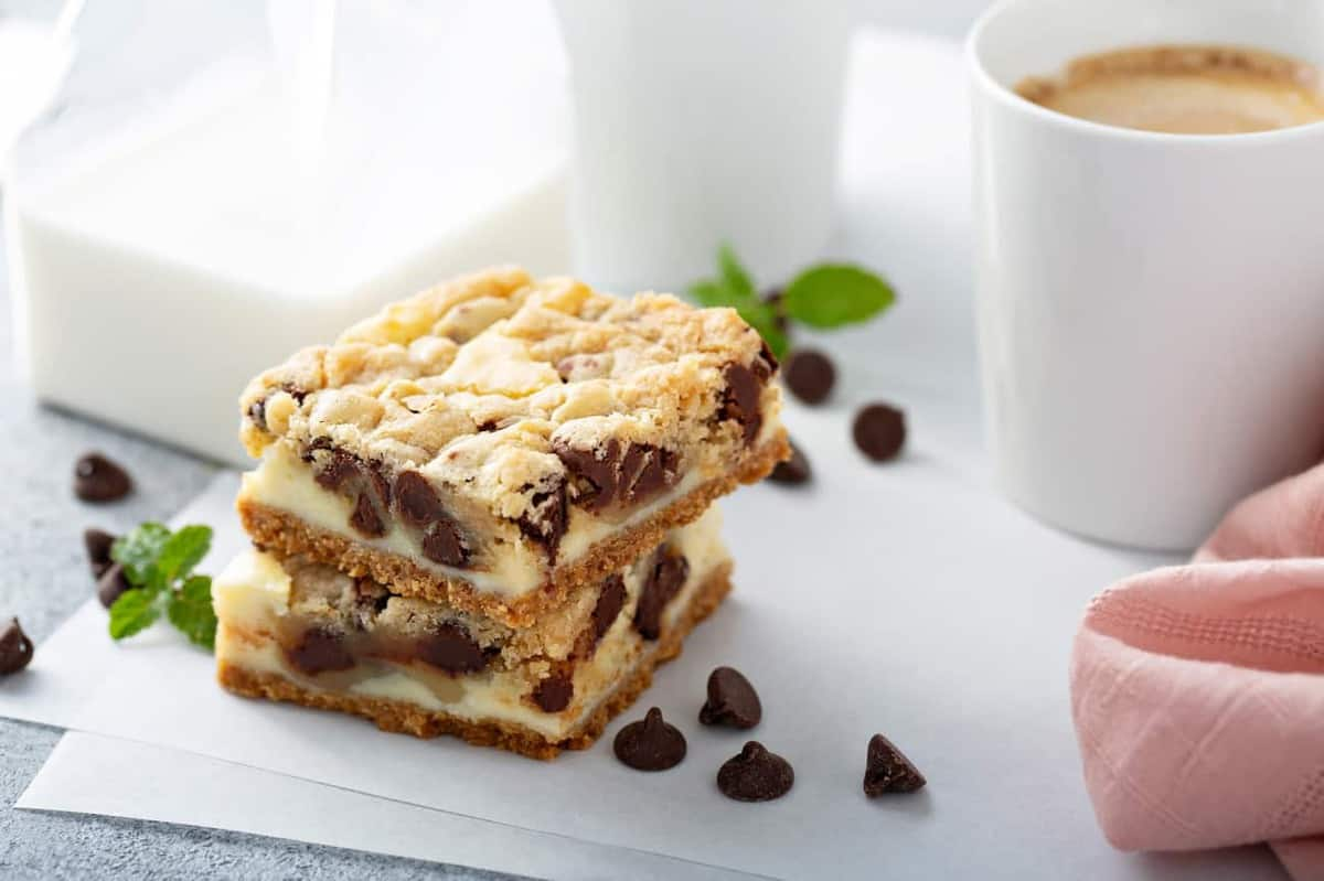 Two sliced cookie dough cheesecake bars on a piece of parchment paper next to a cup of coffee