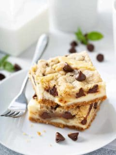 Two plated cookie dough cheesecake bars next to a fork