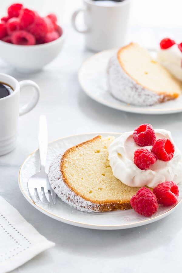 Slice of cream cheese pound cake topping with whipped cream and fresh raspberries next to a fork on a plate