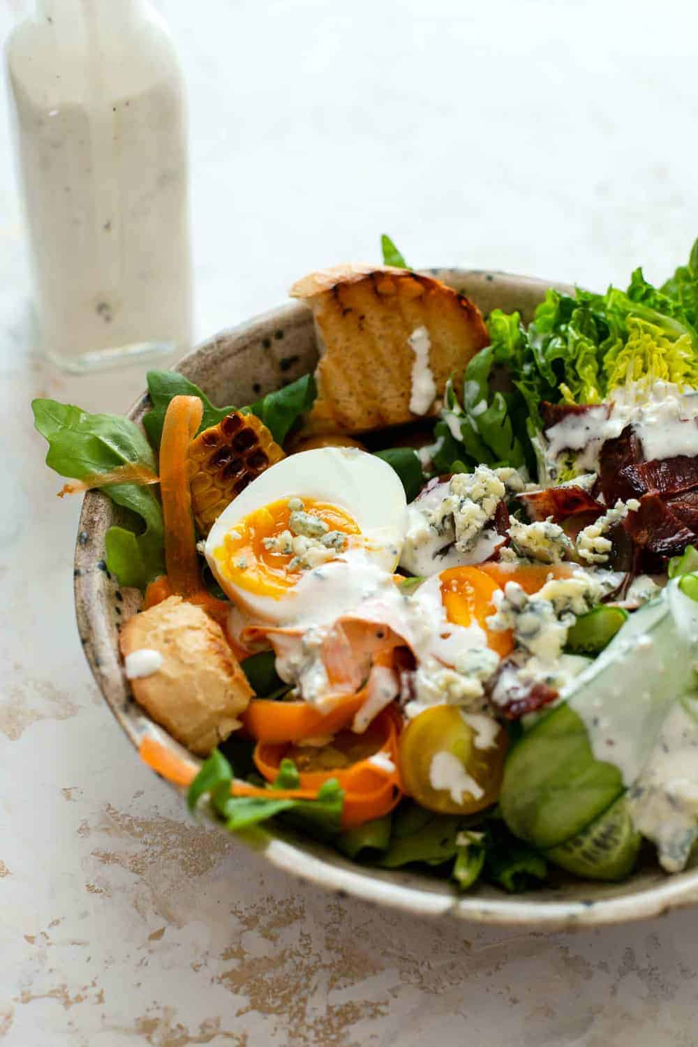 Summer salad dressed with homemade blue cheese dressing next to a bottle of blue cheese dressing