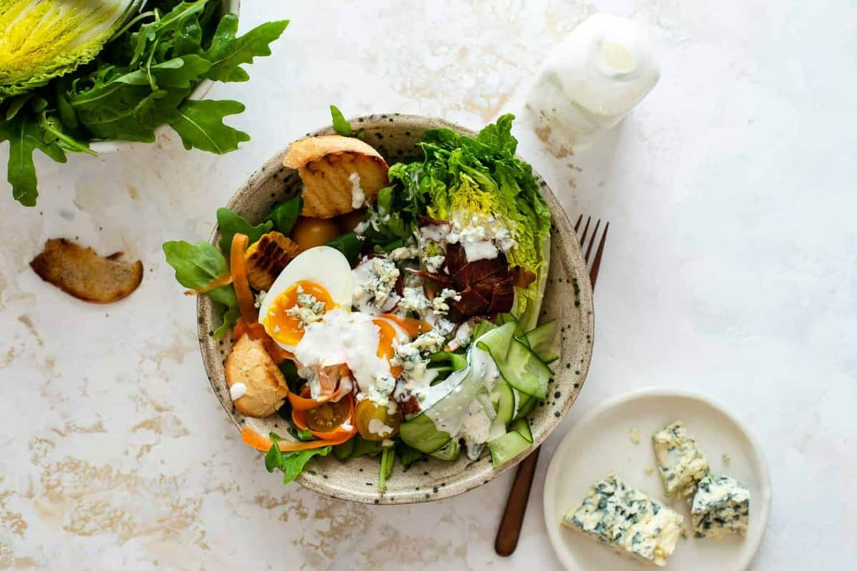 Salad dressed with blue cheese dressing next to blue cheese and a bottle of dressing