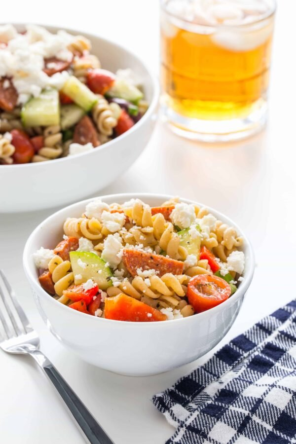 Greek Pasta Salad is loaded with fresh vegetables, feta cheese, pepperoni and a homemade Greek dressing to create the best pasta salad you'll ever eat. Perfect for summer barbecues!