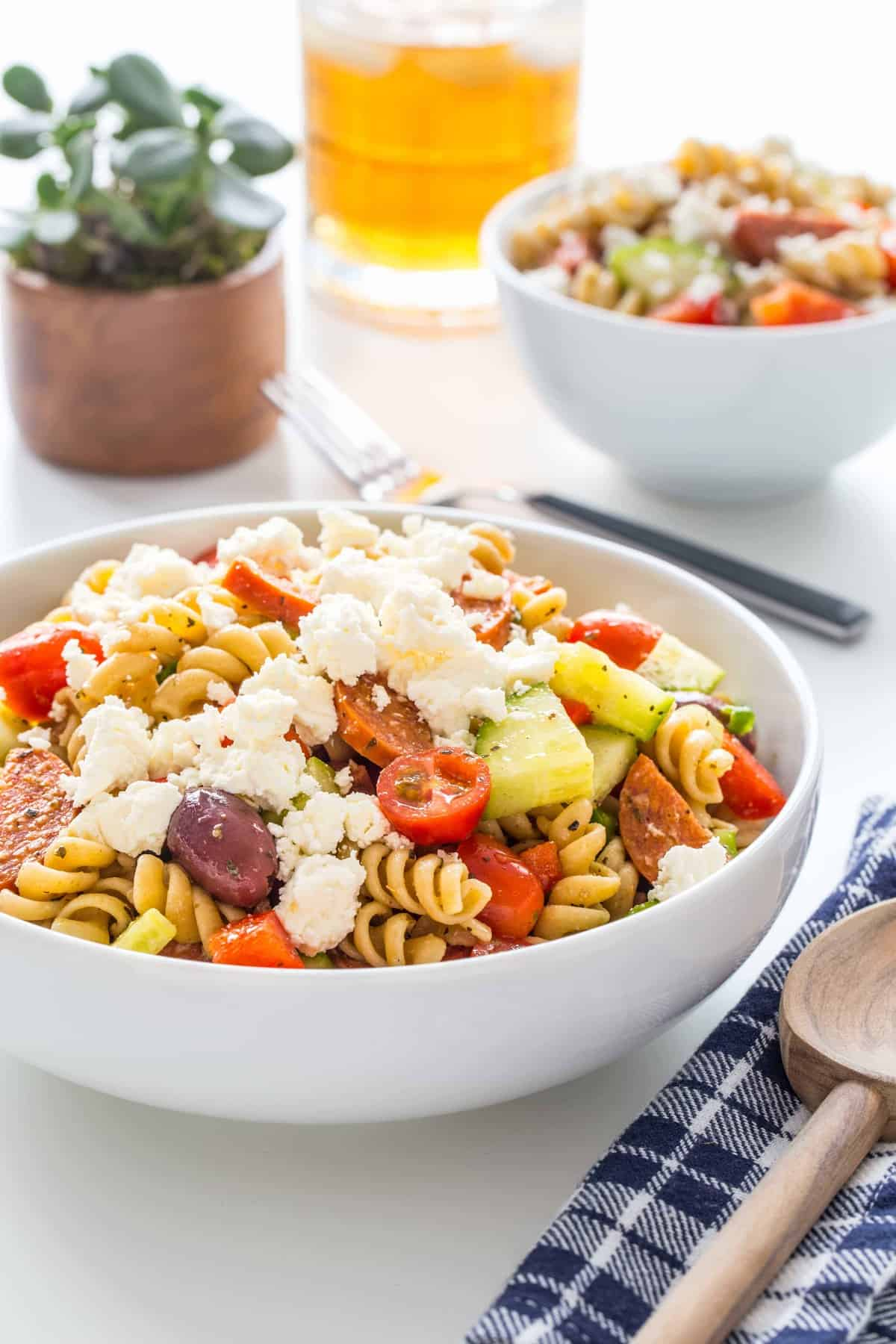 Greek pasta salad topped with feta cheese in a bowl next to a plaid napkin with a wooden spoon
