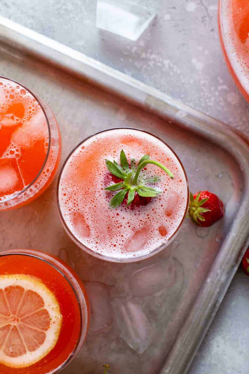 Overhead view of glasses of strawberry lemonade on a sheet tray