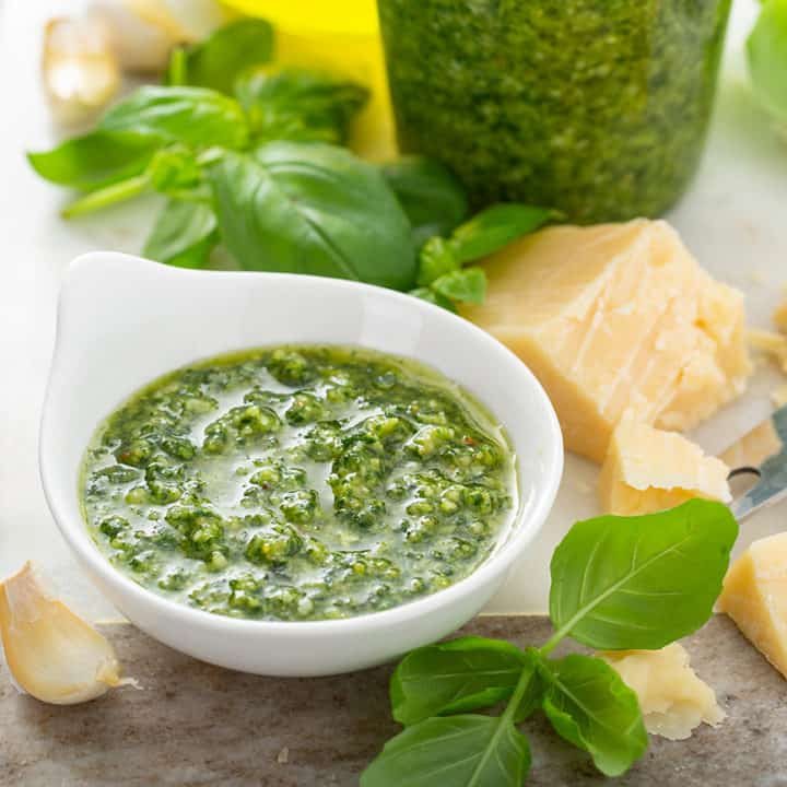 Small white bowl filled with basil pesto on a marble board surrounded by chunks of parmesan cheese and basil leaves