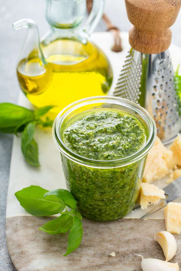 Glass jar filled with basil pesto on a cutting board