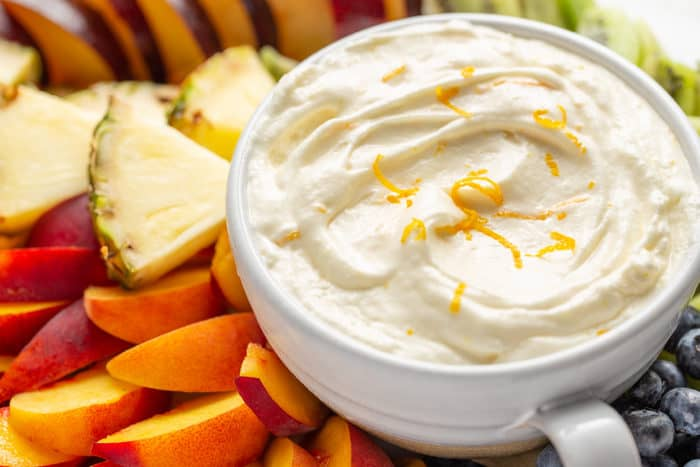 Close up of orange fruit dip in a white bowl, surrounded by cut fresh fruit