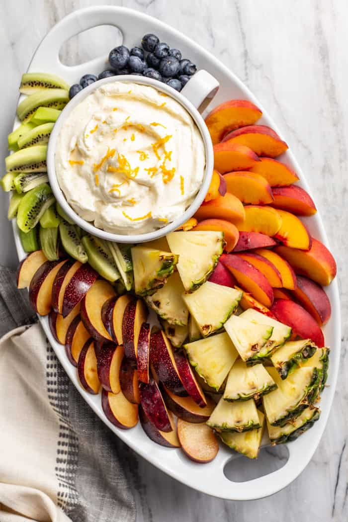 Overhead view of a bowl of orange fruit dip on a platter filled with assorted fresh tropical fruits