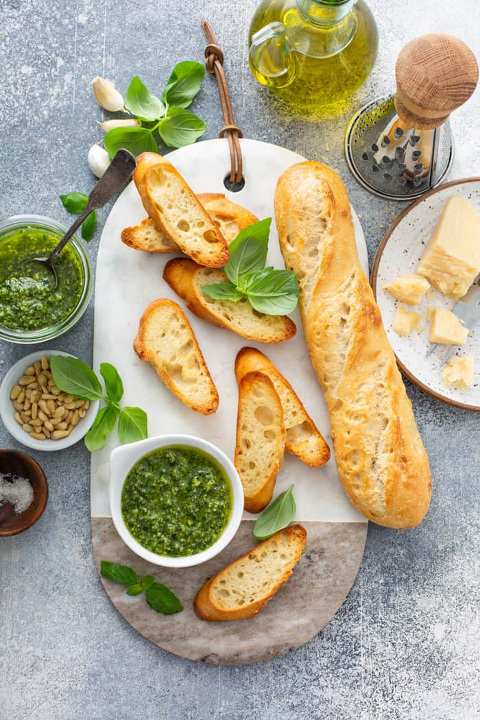 Overhead view of slices of baguette and a bowl of basil pesto on a marble serving board