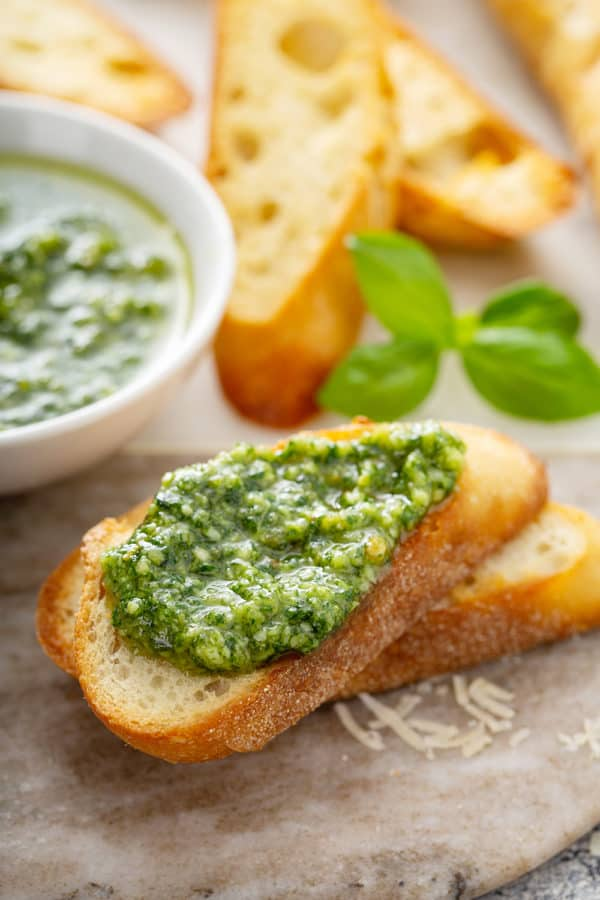 Fresh basil pesto spread on top of a slice of baguette