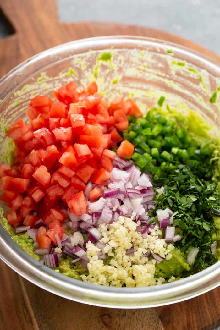 Tomato, onion, garlic, jalapeno and cilantro being added to mashed avocado in a glass mixing bowl