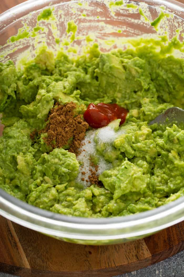 Salt, cumin, and sriracha being added to mashed avocado and lime in a glass mixing bowl