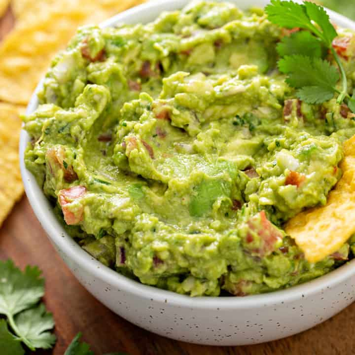 Tortilla chip in a white bowl filled with guacamole