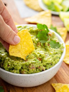 Hand dipping a tortilla chip into a bowl of spicy guacamole