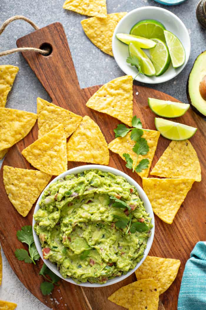 Overhead view of a bowl of spicy guacamole on a wooden board, surrounded by tortilla chips and slices of lime