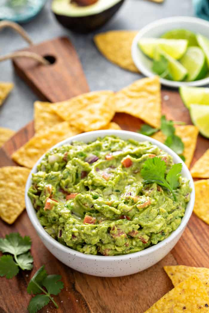 White bowl filled with spicy guacamole set on a wooden board, surrounded by tortilla chips